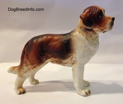 The right side of a brown and white Saint Bernard figurine. The figurines ears are hard to differentiate from its head at this angle.