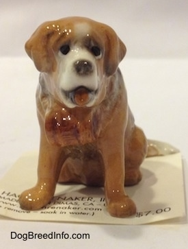 A brown with white figurine of iniature Saint Bernard. The figurine has black circles for eyes.