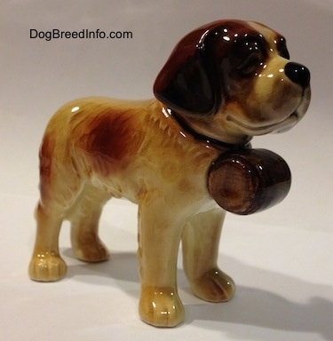 The front right side of a porcelain Saint Bernard figurine. The figurine is glossy.
