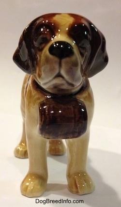 A white with dark tan porcelain Saint Bernard dog figurine. The figurine is wearing a barrel collar.