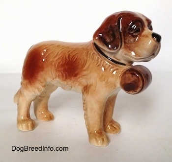 The front right side of a white with brown Saint Bernard figurine. This figurine has fine hair details along its body.