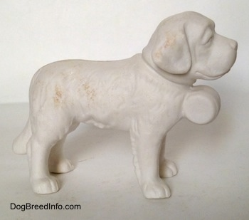 The right side of a figurine of a porcelain white bisque Saint Bernard. The figurine has fine hair details.