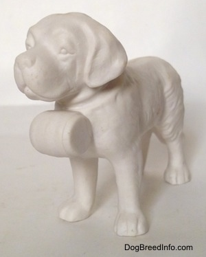 The front left side of a porcelain white bisque Saint Bernard figurine. The figurine has a barrel on its collar.