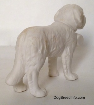 The back right side of a white bisque porcelain Saint Bernard figurine. From this angle it is hard to differentiate the ears of the figurine from its head.