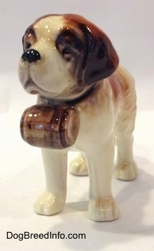 The front left side of a porcelain figurine of a white with brown Saint Bernard. The figurine has brown ears.