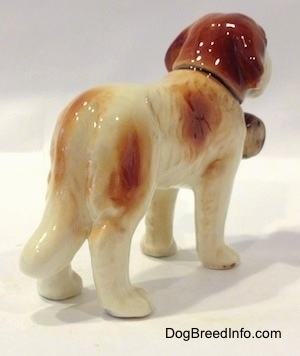 The back right side of a figurine of a white with brown Saint Bernard. The figurine is very glossy.
