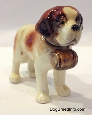 The front right side of a white with brown porcelain Saint Bernard figurine. The figurine has a barrel under its head.