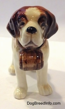 A figurine of a white with brown porcelain Saint Bernard. It is hard to see the black eyes of the figurine.