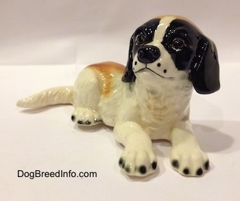 A white and brown with black figurine of a Saint Bernard laying down. The figurine has black tipped nails.