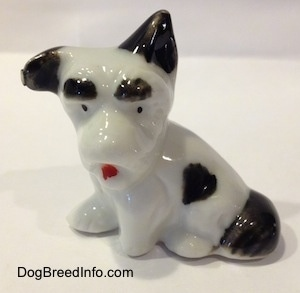 A white and black figurine of a bone china Schnauzer in a sittin pose. The figurine has black circles for eyes and a red tongue.