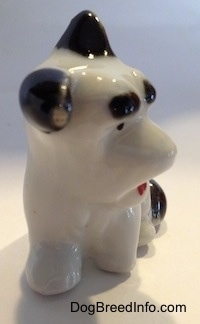 The front of a white with black bone china figurine of a Schnauzer. The figurine has black ears. One is flooped over and the other is standing.