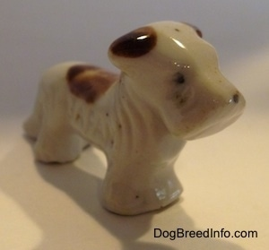 The front right side of a bone china white with brown Schnauzer figurine. The legs of the figurine are attached.