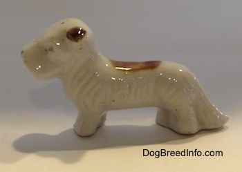 The left side of a figurine of a white with brown bone china Schnauzer. The ears of the figurine is brown.
