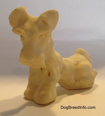 The front left side of a figurine of a Miniature Schnauzer sitting. The figurine is made out of clay.