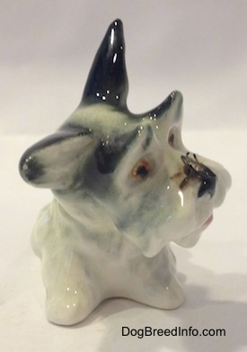 A figurine of a white with black miniature Schnauzer figurine in a sitting position. There is a fly on its nose.