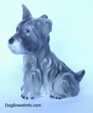 The left side of a grey and white miniature Schnauzer sitting figurine. The figurine has fine hair details.