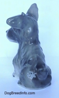 The back left side of a grey and white figurine of a miniature Schnauzer sitting. The figurines tail is hard to see at this angle.