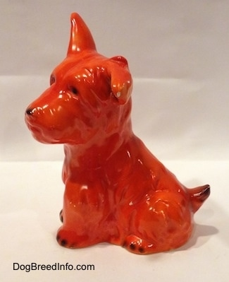 The left side of an orange Schnauzer figurine sitting. The figurine has one ear up and one ear flopped to the side.