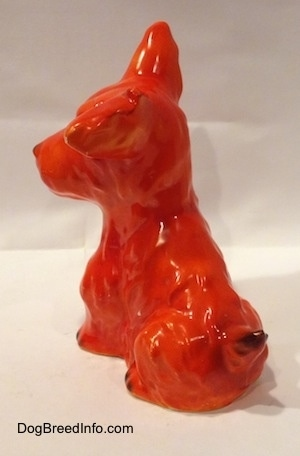 The back left side of a figurine of an orange miniature Schnauzer sitting. The tail of figurine is arched up and it has a black tip.
