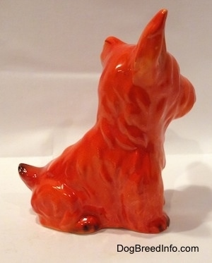 The right side of an orange miniature Schnauzer figurine sitting. The figurine has fine hair details.