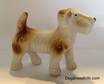 The right side of a white with brown bone china Schnauzer figurine. The figurine has black circles for eyes and a nose.