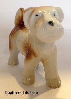 A white with brown figurine of a bone china Schnauzer. The figurine has short legs.