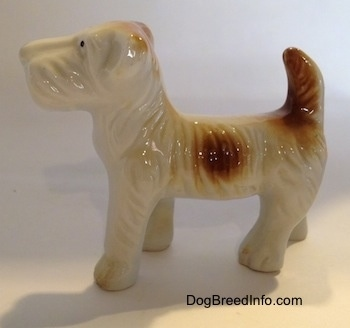 Vintage bone china Schnauzer figurine with natural ears, an undocked tail and a parti coat. Side view.