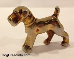 The front left side of a bone china figurine of a Schnauzer painted in gold. The figurine has small flopped over ears.