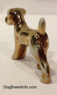 The back left side of a bone china figurine of a Schnauzer that is painted in gold. The tail of the figurine should be arched in the air.
