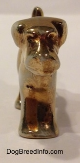 A bone china Schnauzer figurine that is painted gold.