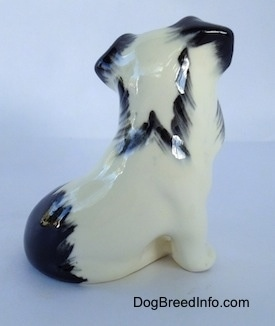 The right side of a parti-color ceramic Miniature Schnauzer sitting figurine. The figurine has a black spot above its tail.