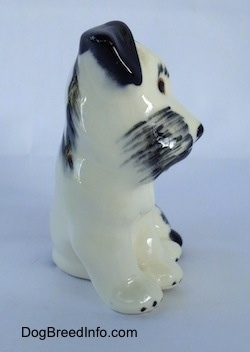 The front of a miniature parti-colored ceramic Miniature Schnauzer figurine in a sitting position.