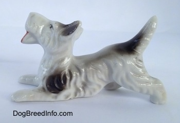 The left side of a white with black bone china Schnauzer figurine. The figurine has fine hair details along its body and legs.