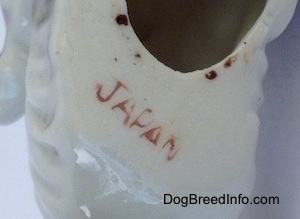 Close up - The underside of a bone china Schnauzer figurine. There is the red stamp of Japan on the underside.