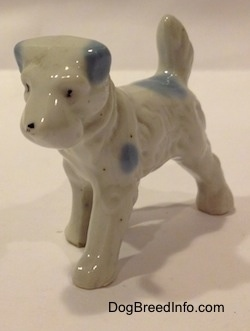 The front left side of a white with blue bone china Miniature Schnauzer figurine. This figurine has black circles for eyes.