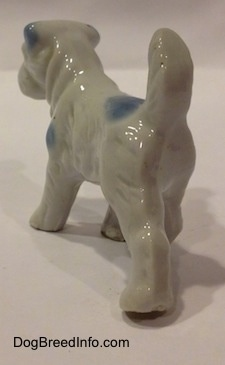 The back left side of a bone china Miniature Schnauzer figurine in a standing pose. The legs of the figurine are medium length.