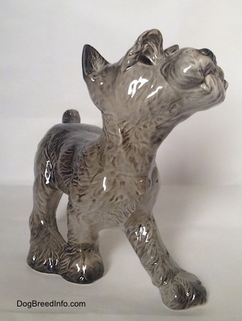 The front left side of a grey with white figurine of a Schnauzer puppy. The figurine has fine hair details.