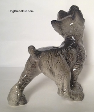 The back right side of a grey with white Schnauzer puppy figurine that is walking. The figurines tail is arched up.