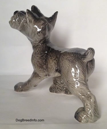 The back left side of a grey with white figurine of a Schnauzer puppy. The figurine is glossy.