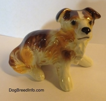 The front right side of a white with brown porcelain Scotch Collie dog figurine in a sitting position. The figurine has black circles for eyes and it has a line for a mouth.