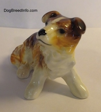 A white with brown porcelain Scotch Collie figurine sitting.