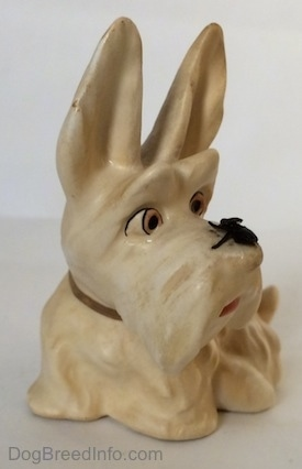 A white and cream figurine of a Scottish Terrier sitting. The figurine has a fly on its muzzle and its mouth painted open.