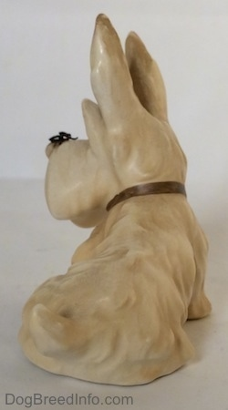 The back left side of a figurine of a white and cream Scottish Terrier sitting. The figurine has a short curly tail.