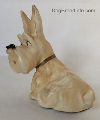The back left side of a white and cream figurine of a Scottish Terrier with a fly on its nose. The figurine has fine hair details along its back.
