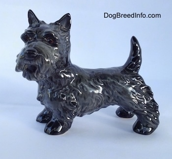 The left side of a black Scottish Terrier figurine. The figurine has fine hair details along its body and legs.