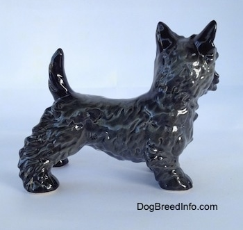The right side of a figurine of a black Scottish Terrier. The figurine has short legs.