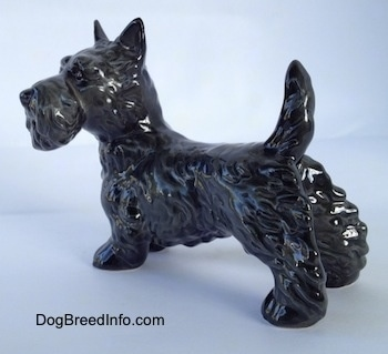 The back left side of a black Scottish Terrier figurine. The figurines body is longer than its legs.