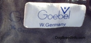 Close up - The underside of a figurine of a Scottish Terrier. There is a sticker on the underside that reads 'Goebel W.Germany'.