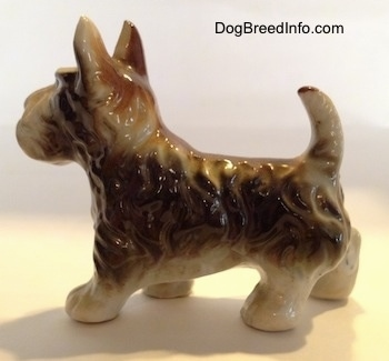 The left side of a figurine of a brown with white bone china Scottish Terrier. The figurine has fine hair details along its head and body.