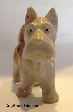 A brown and white bone china Scottish Terrier figurine. The figurine has small black circles for eyes.